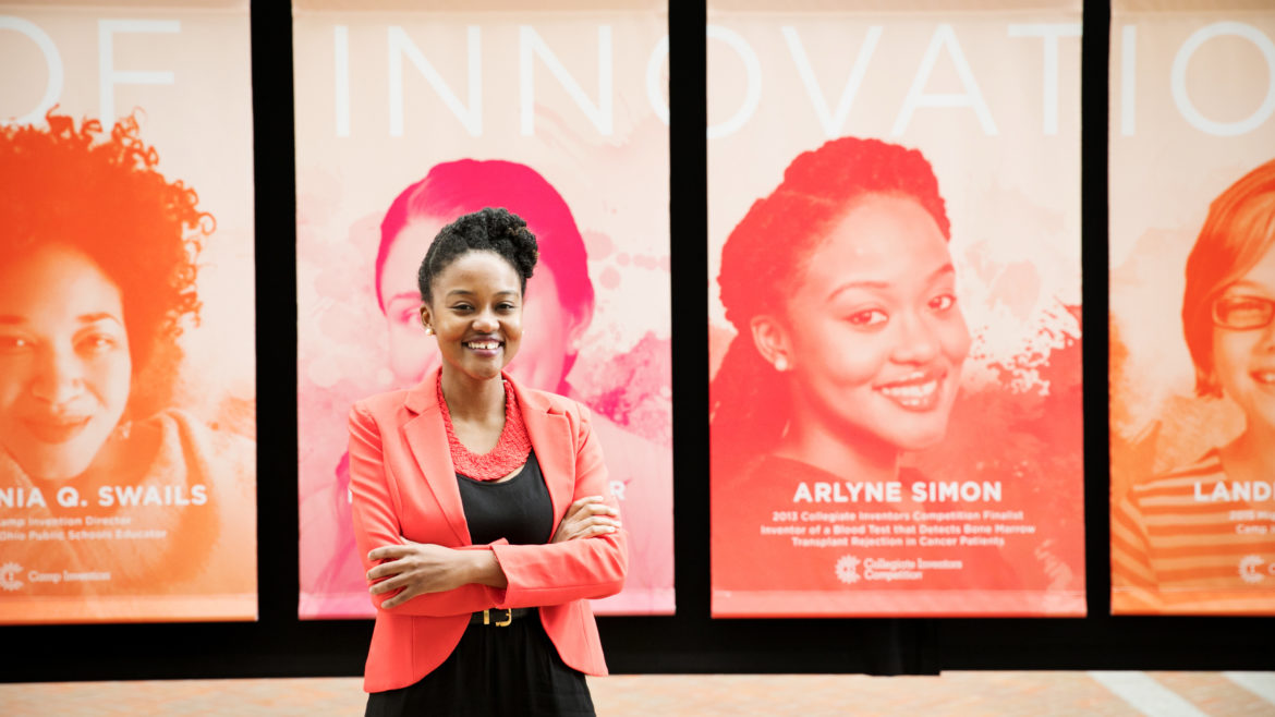 "Photo of Arlyne Simon standing in front of the United States Patent and Trademark Office's ""Women of Innovation"" exhibit"